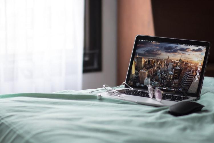 menggunakan laptop di tempat tidur